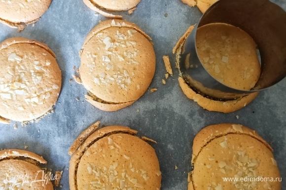 Противень застелить пергаментной бумагой, с помощью кондитерского мешка выдавить тесто, формируя небольшое круглое печенье (11–12 штук). Сверху посыпать рубленым миндалем и отправить в предварительно разогретую до 170°C духовку на 8–10 минут. Затем круглой формой диаметром 6 см еще теплое печенье подогнать под один размер.