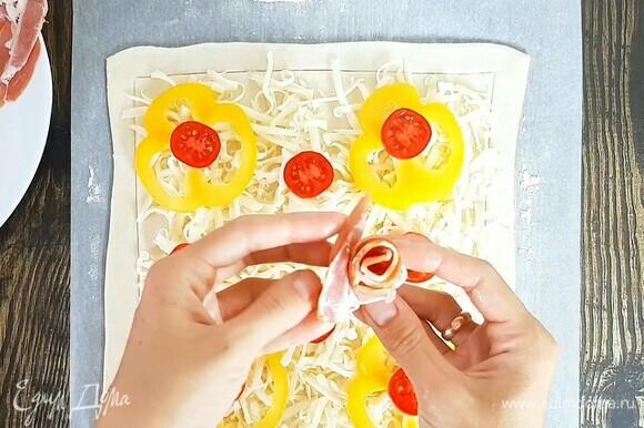 Равномерно распределяем сыр, далее кладем кольца перца и томаты. Ленты бекона скручиваем, формируя розочку, и выкладываем на пирог. Выпекаем в хорошо прогретой духовке при температуре 200°С около 20 минут. Ориентируйтесь по румяности.