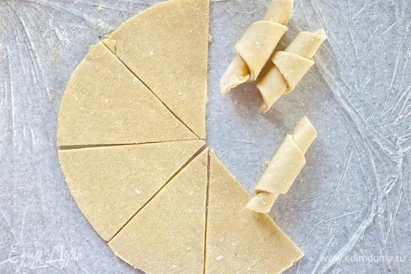 Раскатать в пласт толщиной 0,3 см. Вырезать ровный круг при помощи тарелки. Посыпать сахаром и разрезать его на восемь равных частей. Скрутить каждую часть в рогалик. Окунуть заготовки в сахар и выложить на противень.