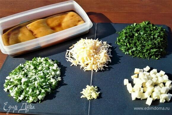 Кальмары заранее размораживаем, чистим, моем, заливаем соевым соусом и оставляем мариноваться. Белый хлеб нарезаем мелкими кубиками. Измельчаем зеленый лук вместе с белой частью, чеснок, шпинат, петрушку, укроп, кинзу — можно взять любую зелень, какая у вас есть в огороде. Сыр натереть на терке. К крошкам хлеба добавляем отварное яйцо, соль, перец, сыр, чеснок, приправу для рыбы, всю нарезанную зелень и кедровые орешки. Друзья, найдите возможность и добавьте в начинку маленькую горсточку орешков, и вы почувствуете чудесный вкус фаршированных кальмаров.