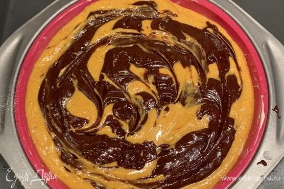 Откладываем 1/3 получившегося теста и смешиваем его с тыквенным пюре, растительным маслом и корицей. К оставшейся массе добавляем шоколадную смесь. Если добавляете орехи, отложите 4–5 ст. л. теста (для верхнего слоя), а в оставшееся добавьте мелко порубленные орехи. В форму выливаем большую часть теста (если добавляете орехи, то тесто с орехами), сверху — тыквенную смесь. Затем ложкой выкладываем оставшееся шоколадное тесто в произвольном порядке. Выпекаем в духовке, разогретой до 180°C, 40 минут.