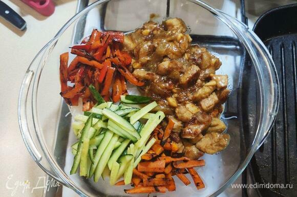 В миску с фунчозой добавить содержимое двух сковородок (мясо с луком и перец с морковью), а также нарезанные соломкой огурцы и зелень.