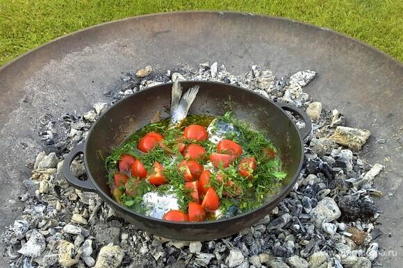 Засыпать рыбу зеленью и помидорами. Положить ветку мяты, чеснок.