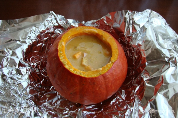 Суп перелить в подготовленную тыкву, накрыть крышкой- хвостиком. Завернуть в фольгу и поставить томиться в разогретую до 190–200°C духовку примерно на 50 минут.