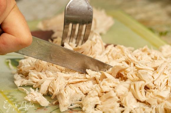 Вареную курицу вытащить из кастрюли, поместить на разделочную доску, нарезать небольшими кусочками, затем снова вернуть в суп.