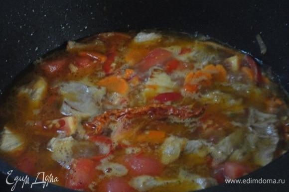 Затем — нарезанные кусочками помидоры и измельченный чеснок. Острый перец целиком положить на картофель. Перемешать, вылить бульон и тушить при медленном кипении 20 минут.