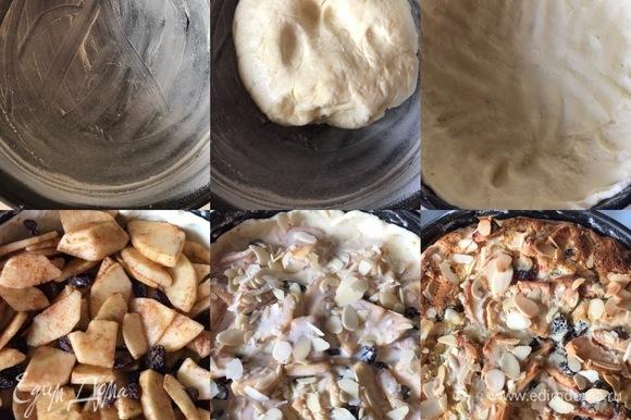 Духовку нагреть до 180°C. Форму диаметром 20 см слегка смазать сливочным маслом и посыпать мукой. Достать тесто из холодильника, руками распределить его по форму и сделать бортики. Если тесто будет сильно липнуть к рукам, то посыпьте немного мукой. Затем в форму переложить яблочную начинку, полить кремом и посыпать миндальными лепестками. Выпекать пирог 50–60 минут.