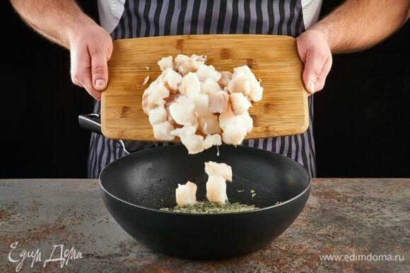 Рыбное филе освободите от костей, нарежьте крупным кубиком, выложите к луку. Добавьте соль и перец. Жарьте рыбу 5 минут до румяности.