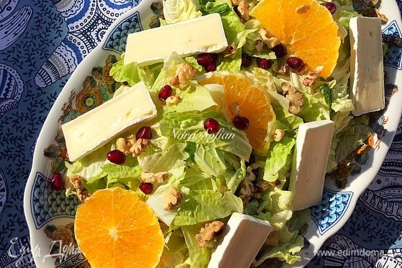 Переложить салат на блюдо, посыпать орехами, гранатом и украсить апельсином и сыром.