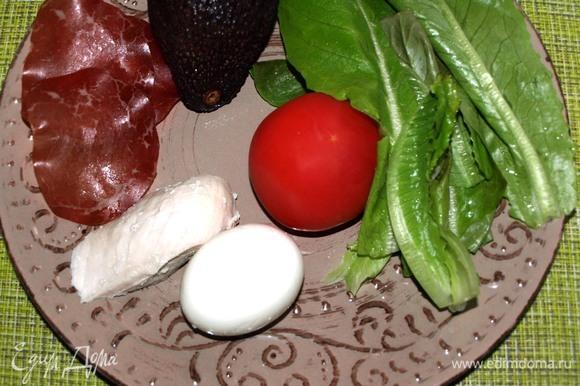 Куриные яйца и куриное филе заранее отварить и остудить. Помидор, куриное филе и яйцо нарезать пластинками. Салат промыть, дать стечь воде и крупно порвать. Авокадо очистить и нарезать дольками.
