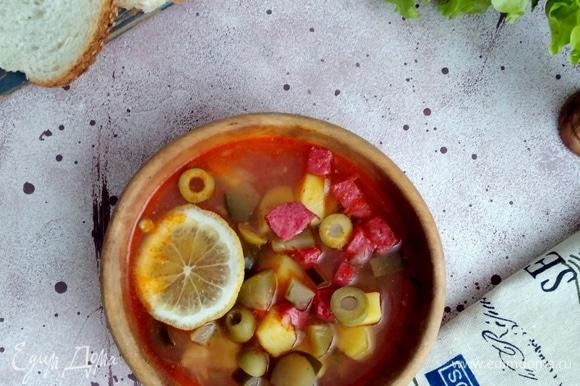 Лимон нарезать дольками. Подавать солянку с лимоном.