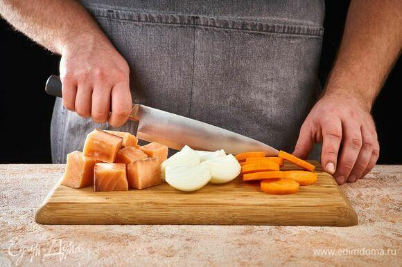 Нарежьте рыбу порционными кусочками. Лук разрежьте пополам, морковь нарежьте кружочками.