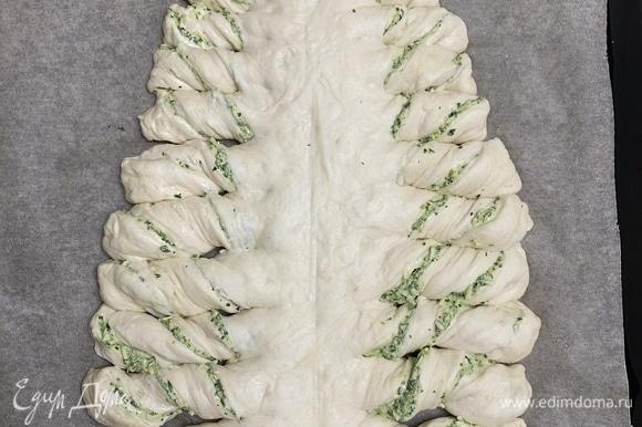Ножом (специальным прибором для пиццы будет удобнее) сделать с обоих краев одинаковые надрезы, не доходя до середины, и завернуть края. Смазать желтком.