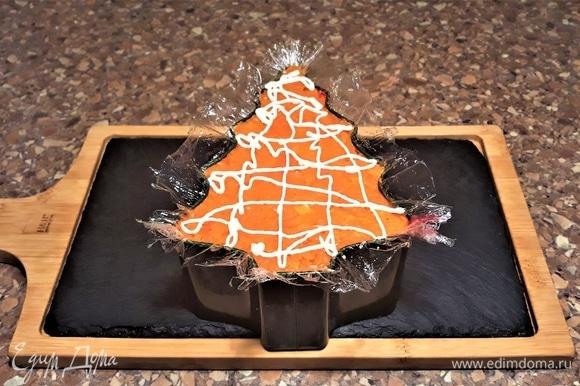 Понадобится форма для слоеного салата. У меня будет форма в виде елки для новогоднего печенья. Есть в классическом варианте приготовления салата правила по последовательности слоев, но я буду укладывать так, чтобы было красиво и красочно в разрезе. Прежде всего формочку надо застелить пищевой пленкой. Укладываем слои: первый — картофель, второй — рыба, третий — лук, четвертый — яичный желток, пятый — свекла, шестой — яичный белок, седьмой — морковь. Каждый слой покрываем тонкой сеткой майонеза. Слой картофеля и свеклы немного солим. Форма у меня маленькая, но глубокая — 6 см. Слои получились толстыми.