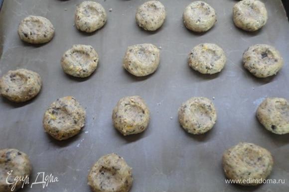 Добавить сухие ингредиенты и перемешать до однородности. Из теста сформировать шарики величиной с грецкий орех, выложить на противень, застеленный пергаментом, и каждый шарик прижать пальцем.