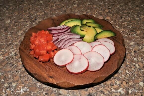Нарежьте очищенное авокадо тонкими дольками, помидоры — маленькими кубиками, удаляя семена и жидкость. Лук очистите, нарежьте перьями. Редис нарежьте очень тонкими кружками. Для крема очистите чеснок и авокадо, нарежьте. Эти ингредиенты смешайте и взбейте погружным блендером до однородной массы. Чтобы авокадо не темнело, надо сбрызнуть его лимонным или лаймовым соком. У меня все же потемнело, и красивый зеленый цвет превратился в цвет хаки.