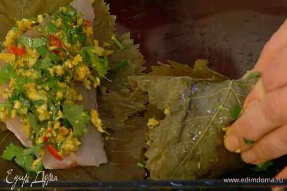 Филе рыбы нарезать порционными кусками, уложить каждый на несколько виноградных листьев, сверху выложить пряную смесь, свернуть в рулетик и скрепить зубочистками.