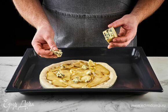 Выложите на тесто карамелизированную грушу. Сверху — кусочки горгонзолы. Выпекайте пиццу в разогретой до 250°C духовке 12–15 минут.
