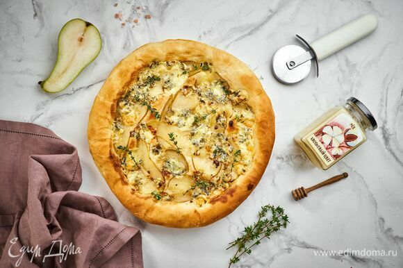 Достаньте пиццу, положите сверху несколько веточек тимьяна и подавайте изысканное угощение к столу.