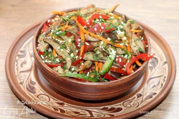 Перед подачей выкладываем салат в красивое блюдо и посыпаем оставшейся зеленью и обжаренным на сухой сковороде кунжутом.