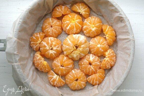 В форму выложить половинки мандаринов срезом вниз.