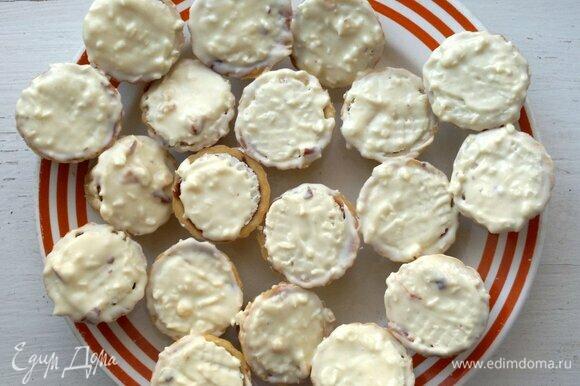 Достать из морозилки пирожные. Смазать с помощью кисточки нижние части, покрытые вафельной крышечкой. Поставить заготовки в морозилку еще на 5 минут.