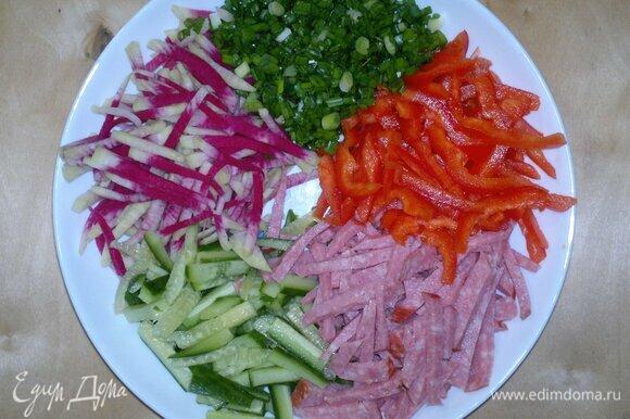На тарелку для подачи выложить по кругу нарезанные продукты.