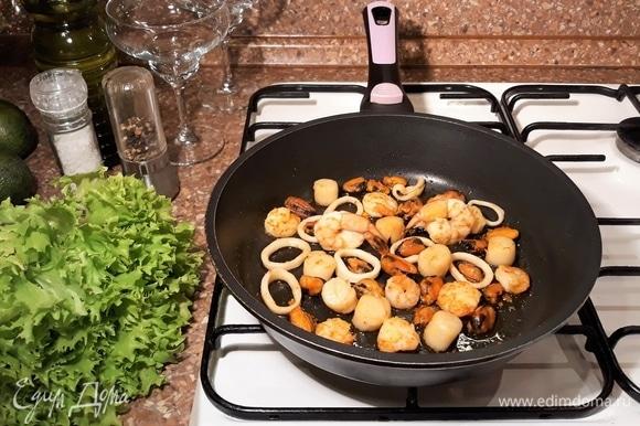 Морепродукты откинуть на сито. Зубчик чеснока очистить, нарезать на пластины. Нагреть сковороду, влить оливковое масло и обжарить чеснок. Когда чеснок станет черным, выбросить его, а в чесночное масло закинуть морепродукты и обжарить их одну минуту.