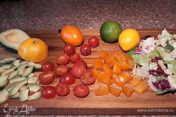 Помидоры черри нарезать пополам. Желтые помидоры нарезать в размер половинок черри. Авокадо очистить, убрать косточку и нарезать тонкими слайсами, сбрызнуть лимонным соком, чтобы не потемнели. Салатный микс (айсберг, романо, радиччио) достать из упаковки.