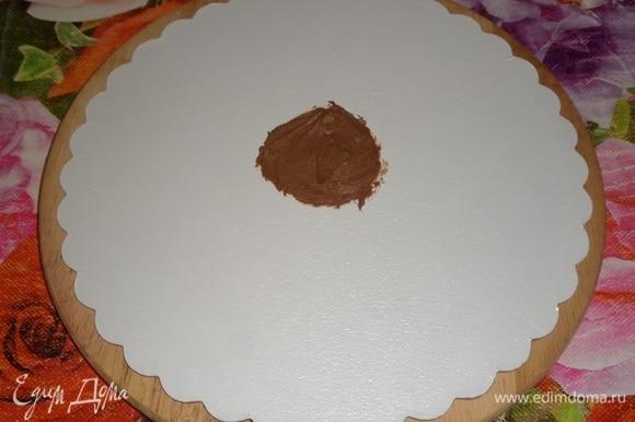 Можем приступать к сборке торта. Шоколадные бисквиты достаем из холодильника, убираем пленку. Вишневую начинку достаем из холодильника. Шоколадный крем достаем из холодильника и выкладываем в кондитерский мешок. Подложку для торта протираем салфеткой, смоченной спиртом. В центр подложки выкладываем 1 ч. л. шоколадного крема.