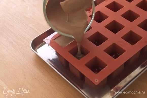 Извлеките формы с малиновым желе из морозильника. Поверх желе налейте шоколадную массу, заполнив форму до конца. Поставьте формы в морозильную камеру на 1 час.