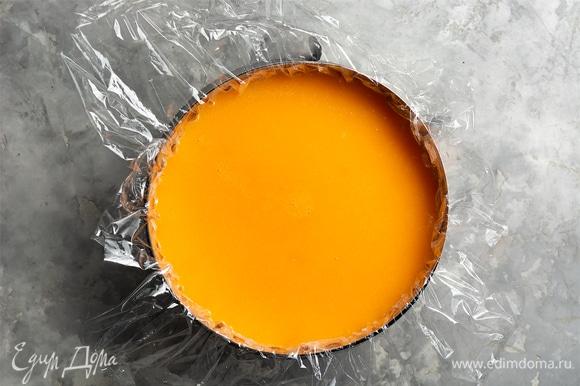 Достать форму с чизкейком из морозилки (или холодильника), снять пленку, поверх залить мандариновым пюре. Накрыть пленкой и убрать в холодильник на 6–8 часов, до полного застывания (лучше — на ночь).