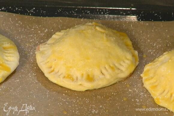 Выложить печенье на противень, выстеленный бумагой для выпечки, смазать желтком с молоком и посыпать сверху оставшимся сахаром.