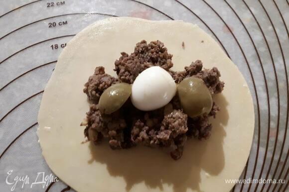 Разделите тесто на 16 частей и раскатайте каждую часть в блинчик толщиной примерно 2 мм. В центр положите начинку, сверху — 1–2 оливки и дольку яйца (у меня на фото целое перепелиное яйцо). Увлажните края теста, защипните края.