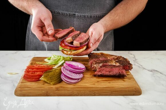 Мясо нарежьте на тонкие кусочки. Соберите бургеры. Положите поочередно все овощи, ломтики стейка и сыр. Накройте второй половиной булочки.