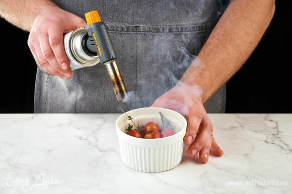 В огнеупорную емкость сложите тимьян, розмарин и помидоры черри. При помощи горелки опалите зелень, накройте емкость крышкой или фольгой.