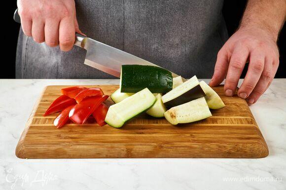 Цукини, болгарский перец и баклажан разрежьте вдоль на крупные куски.