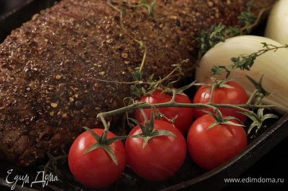 Сковороду-гриль сильно разогрейте, обжарьте мясо со всех сторон до образования корочки. На той же сковороде подрумяньте помидоры черри, четвертинки лука и чеснок, разрезанный пополам вдоль, сверху положите веточки тимьяна.