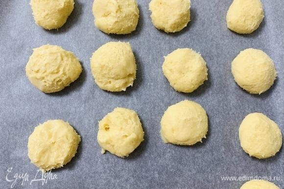 Сразу после холодильника слепить из теста одинаковые шарики диаметром 4–6 см и разложить их на противень, покрытый пекарской бумагой.