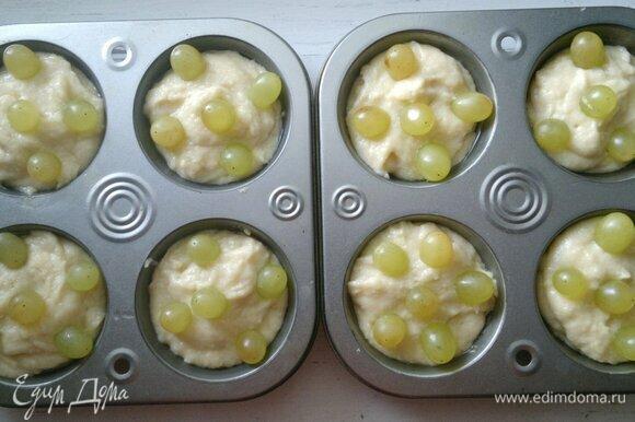В каждый кекс вставить по 5–6 виноградин, слегка утапливая их в тесте.