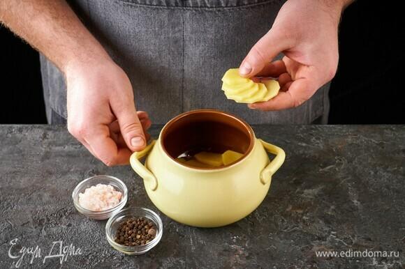 Возьмите горшочки. Выложите слой картошки, посолите, поперчите.