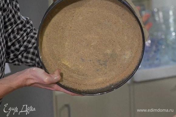 Дно разъемной формы для выпечки выстелить пищевой бумагой, слегка смазать дно и бока сливочным маслом и посыпать сухарями.
