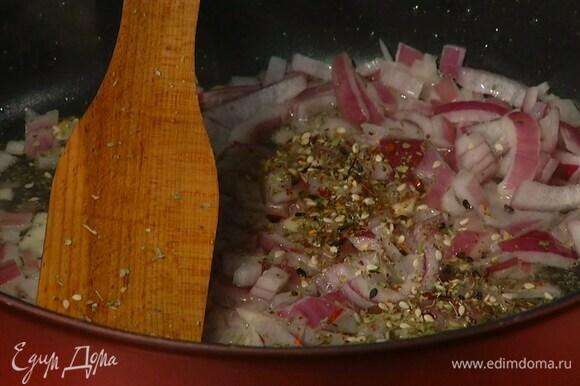 В глубокой сковороде разогреть оливковое масло и обжарить лук с чесноком, затем добавить кунжут, орегано, тимьян, майоран, сладкую паприку и чили, все посолить, перемешать и прогревать на небольшом огне.