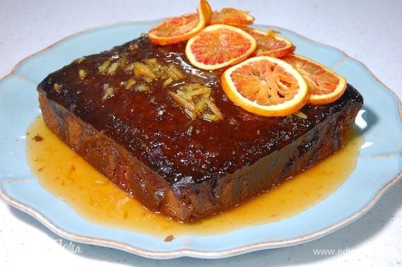 Готовый кекс полить горячим соусом и украсить дольками апельсина.