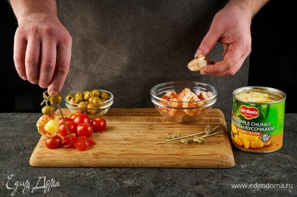 Консервированные ананасы кусочками в соке Del Monte насадите на шпажку вместе с оливками, креветками и помидорами черри.