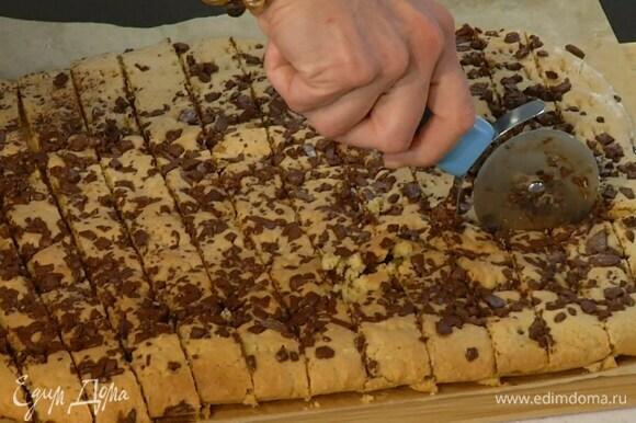 Горячий корж порционно нарезать на печенье.