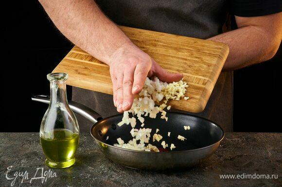 Лук и зубчик чеснока мелко порубите и обжарьте на оливковом масле до золотистого цвета.