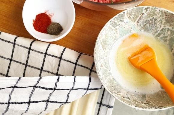 В фарш добавляем специи и зелень, размораживаем тесто и кладем его в мокрое полотенце, чтобы не заветрилось. Сливочное масло, примерно 180 г, растапливаем. Тесто выкладываем на смазанную маслом поверхность и смазываем сами пласты.