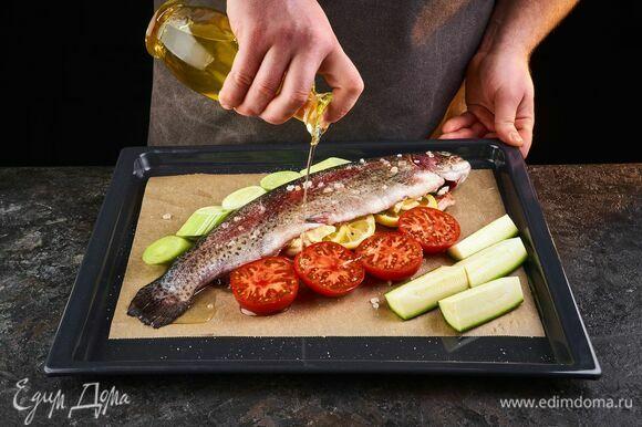 Выложите к рыбе на противень нарезанные овощи: цукини, помидоры, лук-порей. Сбрызните растительным маслом и поставьте в разогретую до 180°C духовку на 25 минут.