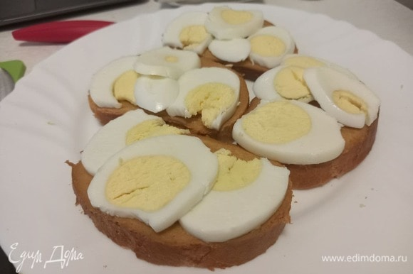 Выкладываем слайсы отварного яйца на хлеб поверх горчицы.